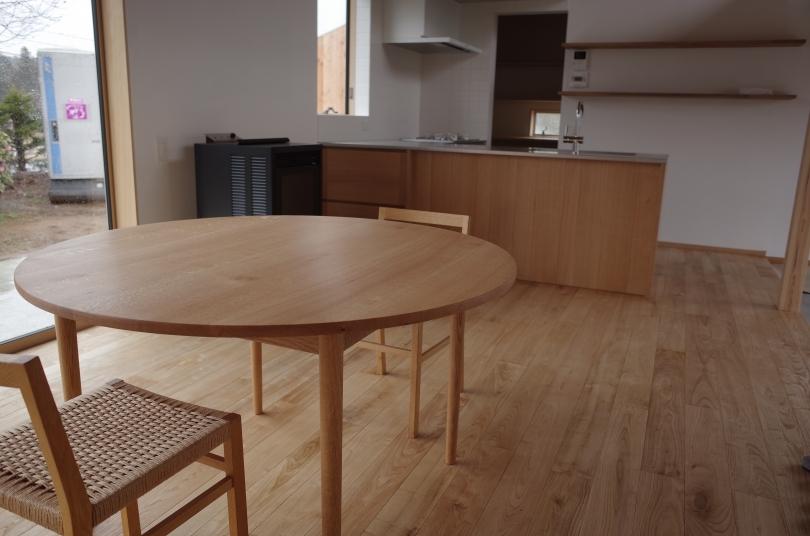 ダイニングテーブルとあわせた、無垢材のL型キッチン。