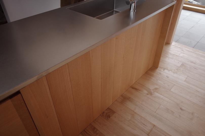 正面の板幅を不規則にした、無垢材のL型キッチン。